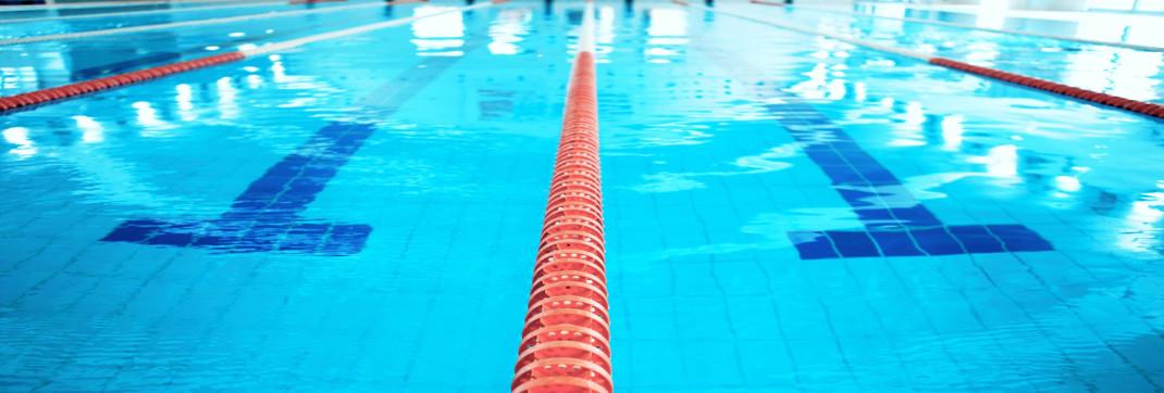 In einem Schwimmbecken ist eine rot-weiße Leine gespannt, welche zwei Schwimmbahnen voneinander trennt.