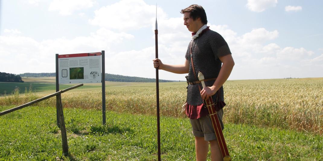 Ein römischer Wachsoldat steht mit einem Speer auf einem Feld.