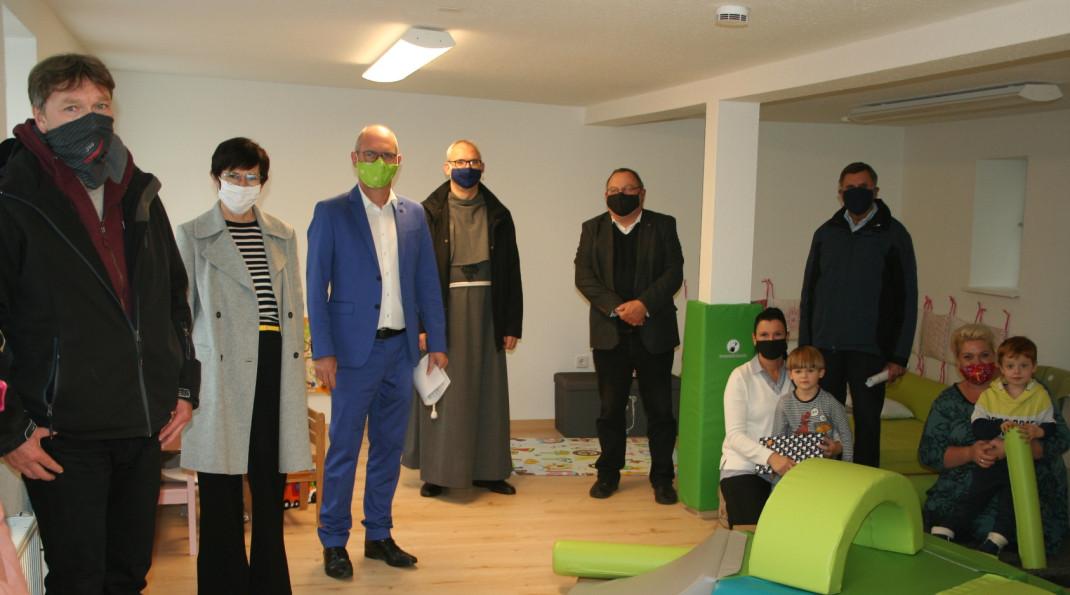 Eine Gruppe der Teilnehmer der offiziellen Einweihung der Kindertagespflege. Darunter befinden sich zwei Kleinkinder.