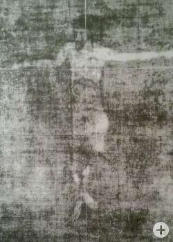 Eine Fotografie des Korporale-Schutztuch, welches mit ultravioletten Strahlen beleuchtet wurde. Darauf sichtbar der Umriss des gekreuzigten Heilands.
