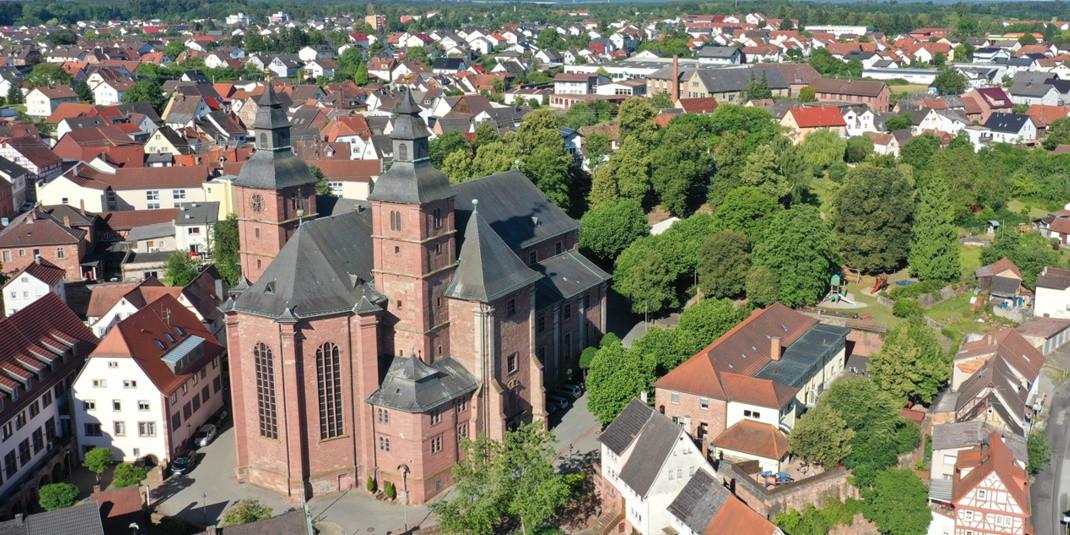 Eine Luftaufnahme der aus rotem Buntsandstein erbauten Wallfahrtsbasilika und dem begrünten Wallfahrtsplatz. Die große Kirche hebt sich deutlich von der Umgebungsbebauung mit kleinen Häusern ab.