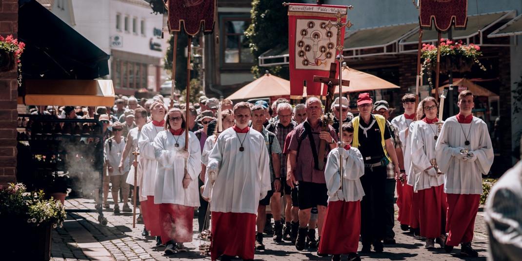Eine Fußprozession zieht durch die Walldürner Altstadt. Sie wird von Ministranten in rot/weißen Gewändern mit Fahnen, Kerzen und Weihrauch begleitet.