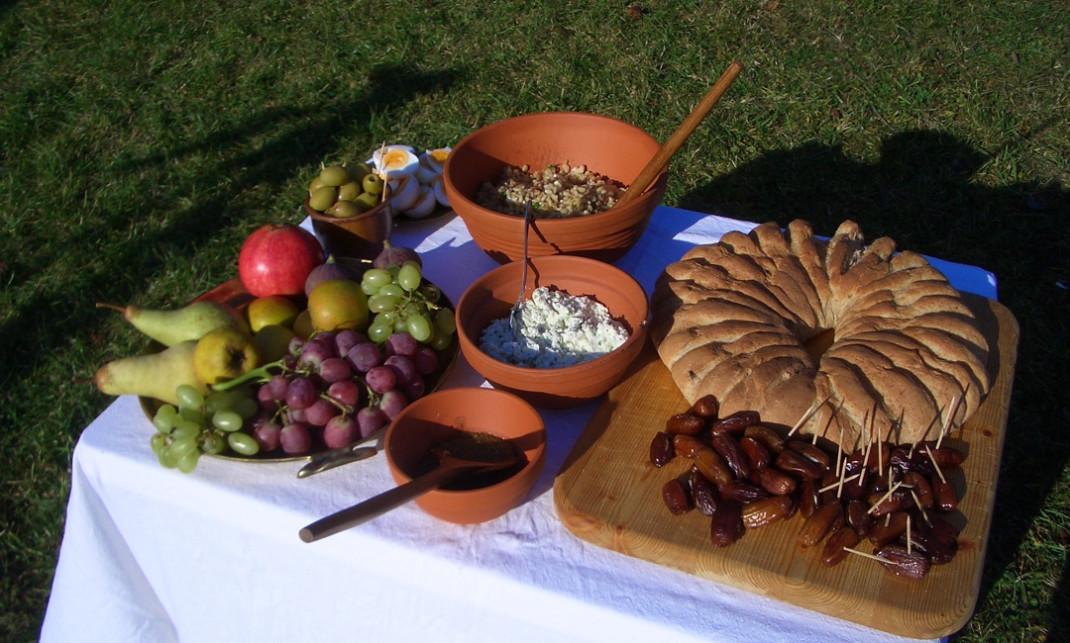 Ein mit römischen Speisen gedeckter Tisch auf einer Wiese.