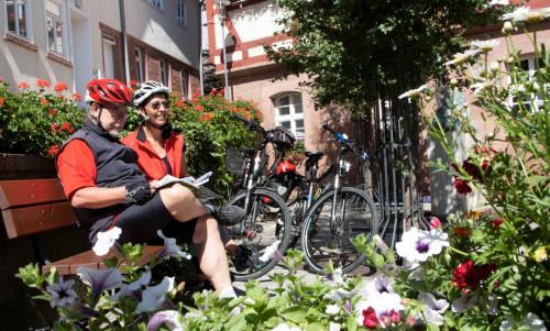 Ein Radfahrerehepaar sitzt auf einer Holzbank vor dem Walldürner Rathaus und studiert eine Karte. Die Räder sind dabei an einen Baum angelegt.