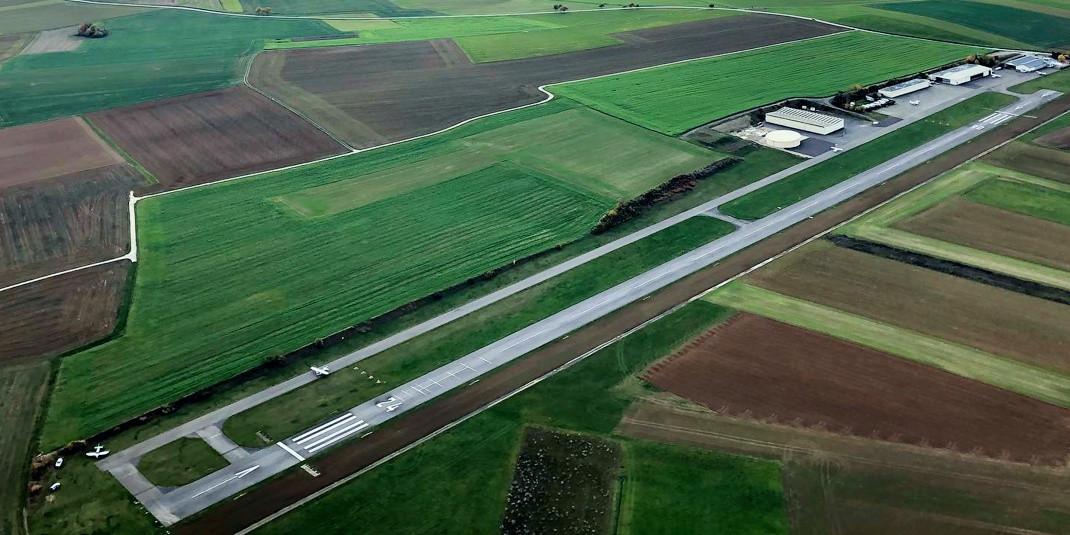Eine Luftaufnahme der Start-/Landebahn des Flugsportclubs Odenwald in Walldürn. Das Areal mit Hangars und Tower ist in grüne und braune Landwirtschaftsflächen eingebettet.
