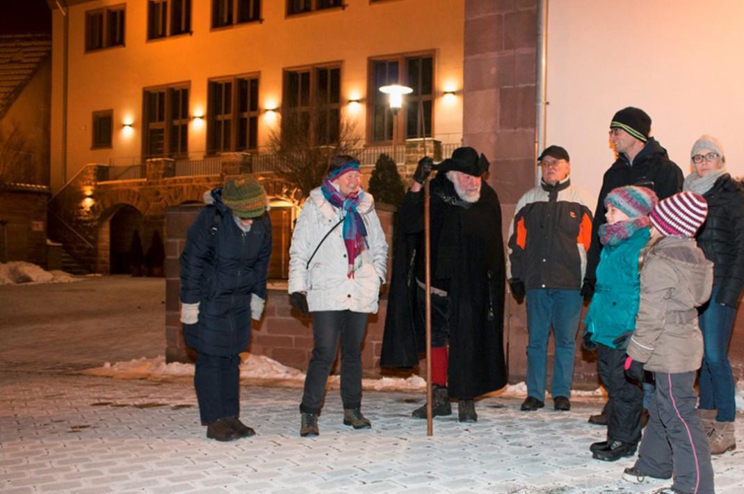 Eine Grupp Menschen begleitet den Walldürner Nachwächter in seinem historischen Kostüm auf dem abendlichen Rundgang.