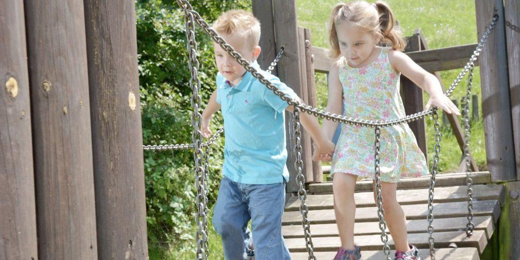 Ein kleiner junge mit blauer Jeans und ein kleines Mädchen im bunten Kleid laufen Hand in Hand über eine Hängebrücke