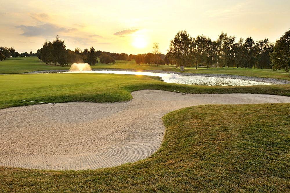 Golfplatz bei Sonnenuntergang mit leuchtendgoldenen Farben und Brunnenspiel im Hintergrund