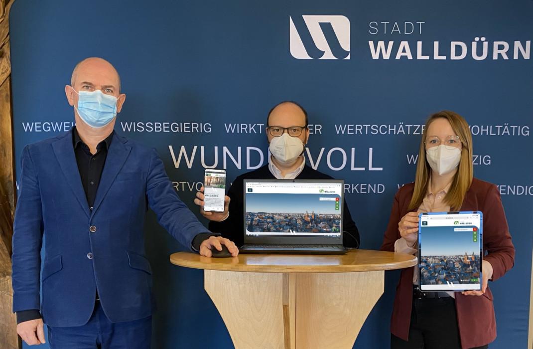 Das Bild zeigt Bürgermeister Markus Günther, Stabsstellenleiter Meikel Dörr und Sina Berberich bei der Freischaltung der neuen Internetseite. In der Mitte steht ein Notebook welches die Seite zeigt. Ebenso auf einem Smartphone und eine Tablet.