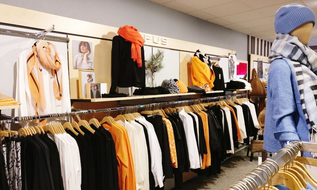 Gehrigmode Geschäftsräume Kleiderstangen mit bunten Kleidungsstücken der Herbst-Wintermode- hauptsächlich in weiß, senf, schwarz im Vordergrund hellblau