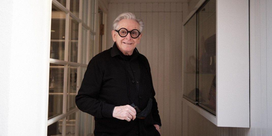 Richard Lang steht lächelnd in schwarz gekleidet im Eingangsbereich seines Hutateliers und trägt eine schwere Hornbrille