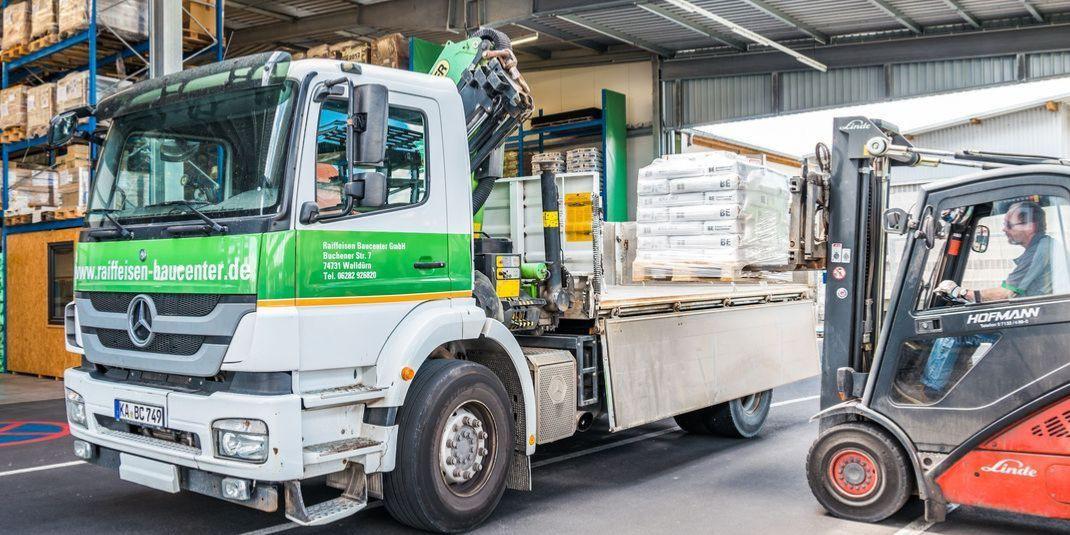 LKW des Raiffeisenbaucenter in grün weiß in einer Lagerhalle bereit zur Lieferung