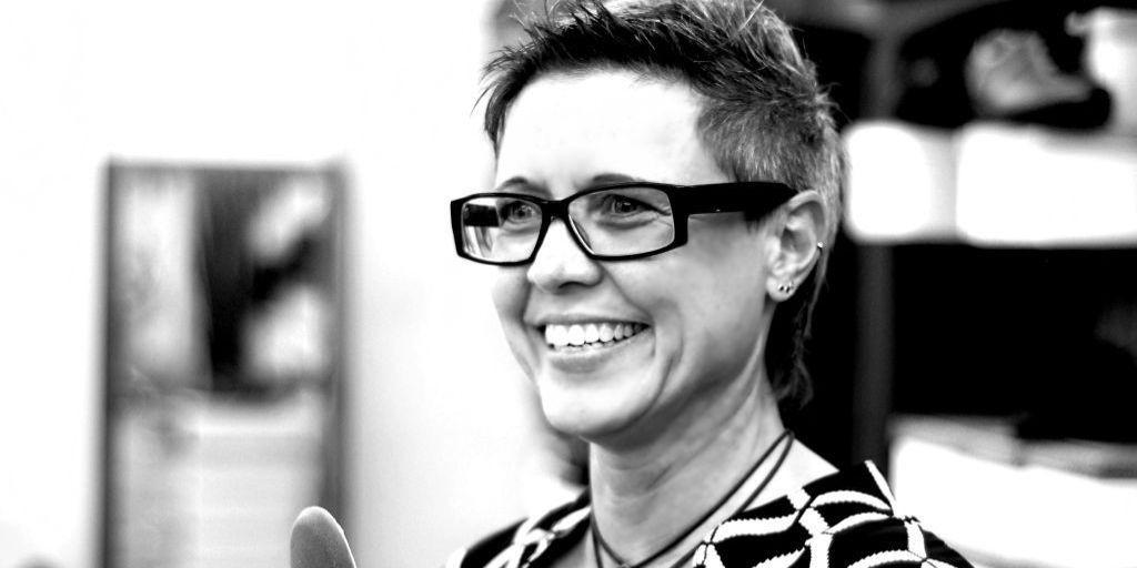 Dini Müller in schwarz weiß im Verkaufsraum von Schuhmueller. Sie lacht und trägt eine schwarze eckige Hornbrille