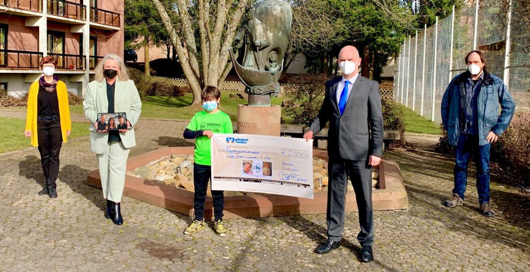 Eine Gruppe Menschen überreicht einen Spendenscheck in Höhe von 2500 Euro