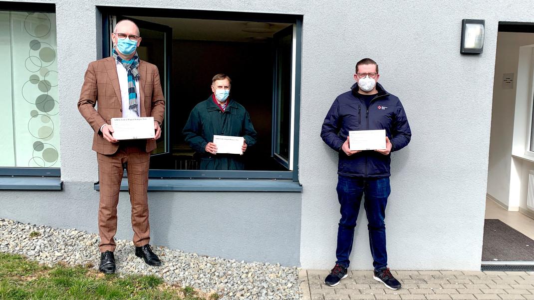 Das Bild zeigt drei Männer mit Mund-/Nasenmaske vor dem kommunalen Corona Testzentrum. Jeder hat eine Packung Schnelltests in der Hand.