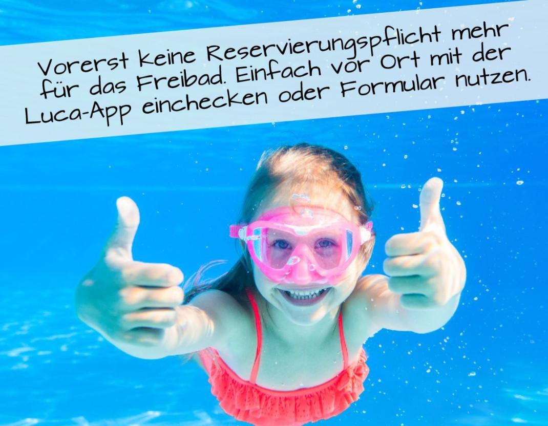 Ein Kind taucht unter Wasser und zeigt lachend mit zwei Daumen nach oben. Dazu der Hinweis, dass für das Freibad keine Reservierung erforderlich ist.