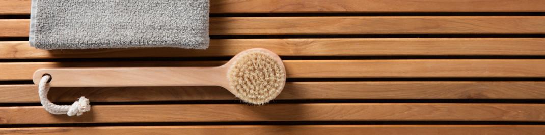 Stilleben einer Bürste auf einer Holzbank, wie man sie in Sanitärräumen findet